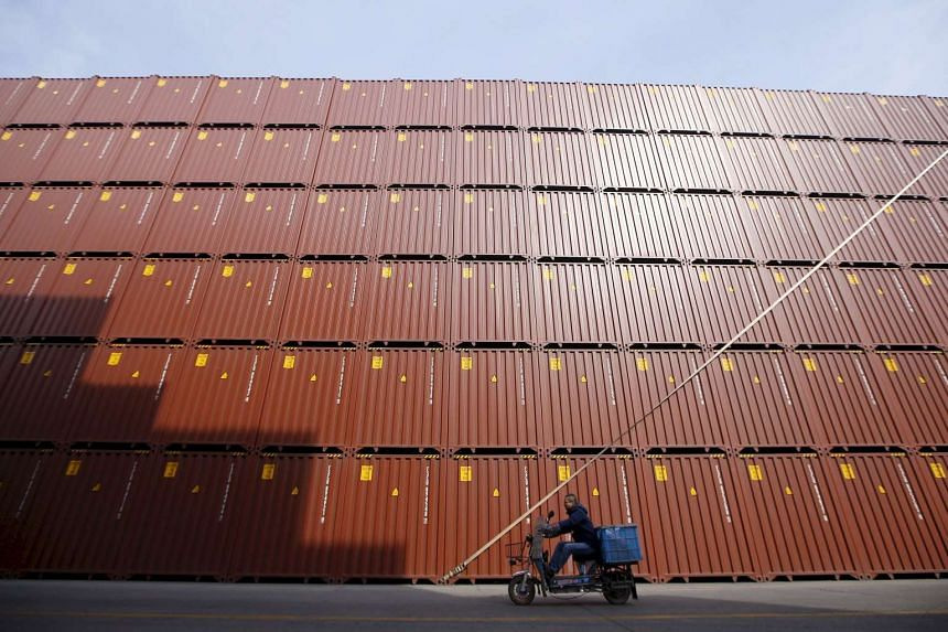 A man rides a vehicle past container boxes at a port in Shanghai.