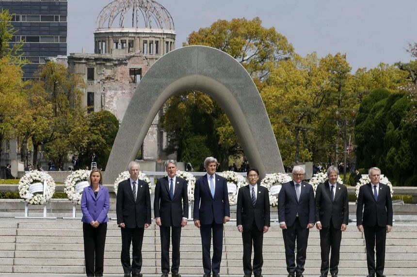 The Group of Seven countries' foreign ministers pose for a group photo session at Hiroshima Peace Memorial Park with viewing the Atomic Bomb Dome (Rear) in Hiroshima.
