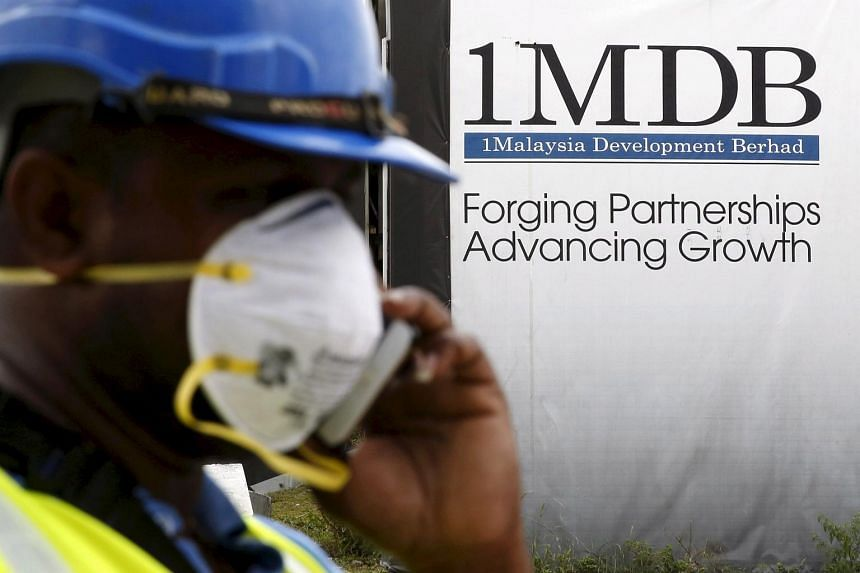 A construction worker talks on the phone in front of a 1Malaysia Development Berhad (1MDB) billboard.