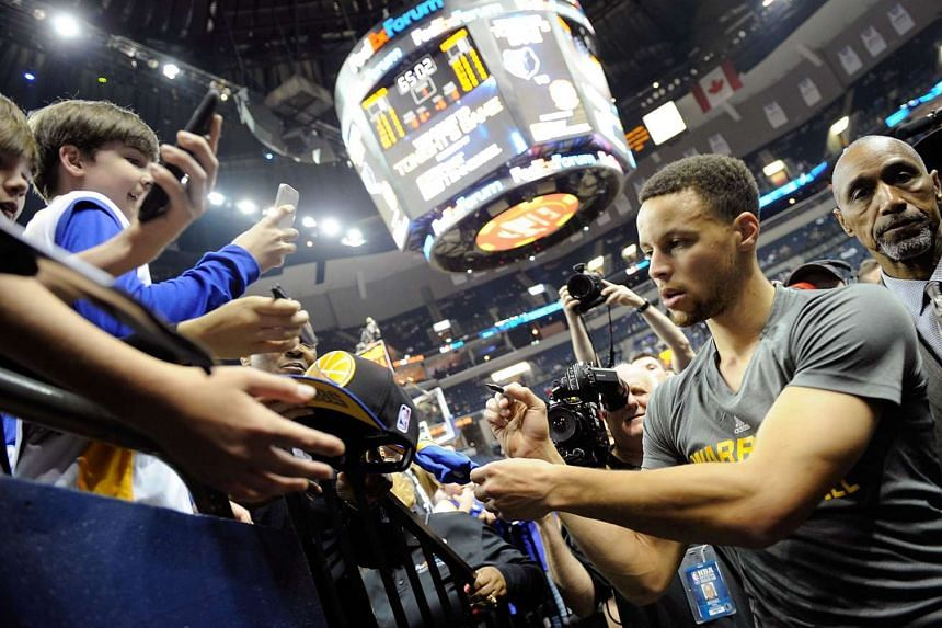 Stephen Curry of the Golden State Warriors signs autographs for fans prior to a game against the Memphis Grizzlies on April 9, 2016