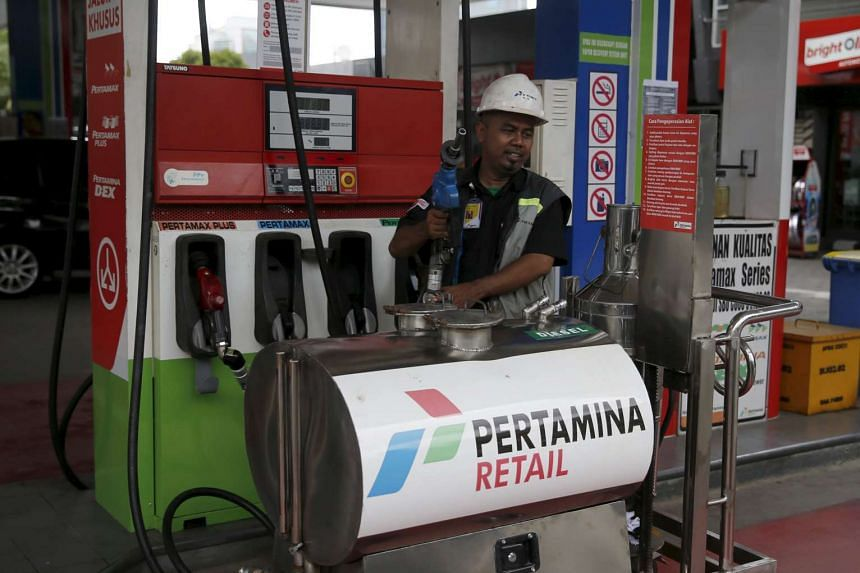 A worker stands by a fuel dispenser a petrol station of state-owned Pertamina in Jakarta, Indonesia, Feb 17, 2016.