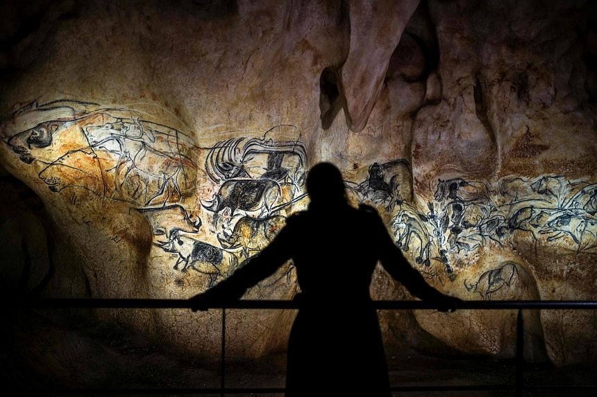 A person looking at part of a full-scale reproduction of frescos found at the cave of Pont-D'Arc on April 8.