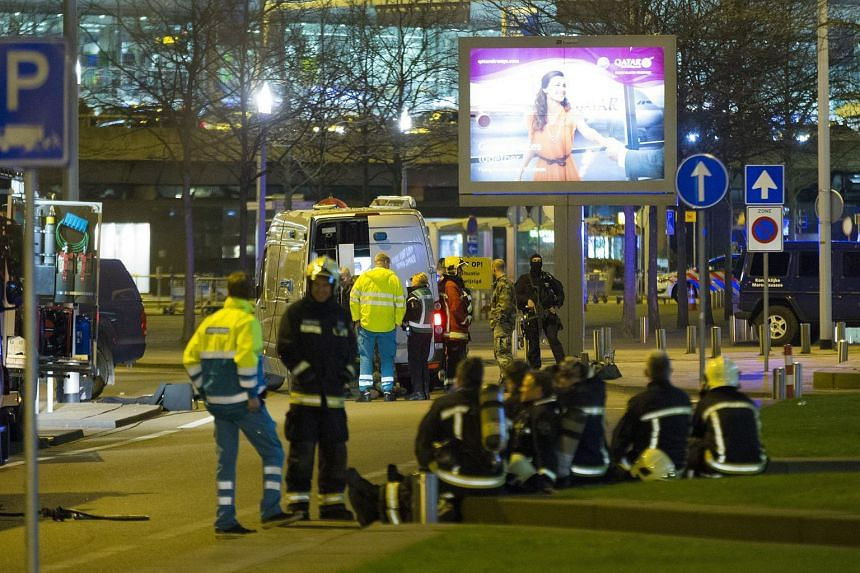 Dutch policemen and rescuers intervening in an evacuated area at Amsterdam's Schiphol Airport on April 12, 2016.