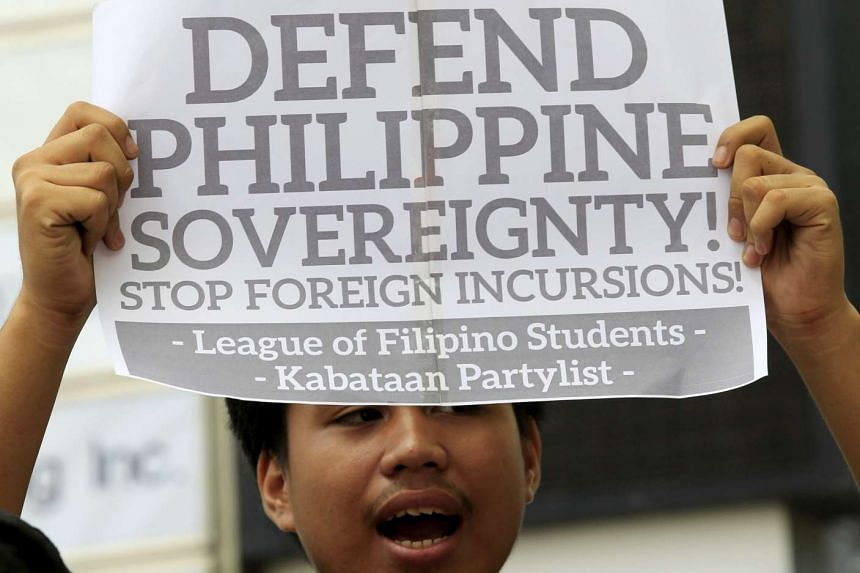 A protestor holds a placard during a rally regarding the disputed islands in the South China Sea, in front of the Chinese Consulate in Makati city, Manila.