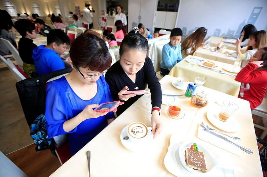 Customers in China's first official Hello Kitty-themed restaurant in Shanghai. From May 1, VAT will replace business tax in sectors such as consumer services, a move expected to cut taxes by over 500 billion yuan (S$104 billion) this year.