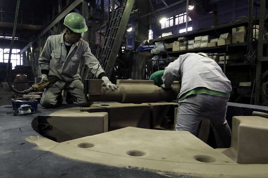Workers making a casting mould at the Tomiwa Chuzo foundry in Japan. The International Monetary Fund cut Japan's growth forecast in half to 0.5 per cent this year while forecasting growth of 3.2 per cent for the global economy. Its previous forecas