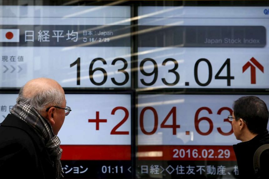 Pedestrians look at an electronic board showing the Japan's Nikkei average outside a brokerage in Tokyo.