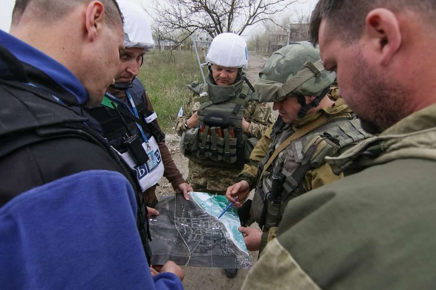 Ukrainian servicemen (right) and Organization for Security and Co-operation in Europe (OSCE) representatives look at a map of the village, in Shyrokine, near Mariupol, Ukraine on April 13. The United Nations has called for the immediate and unconditi