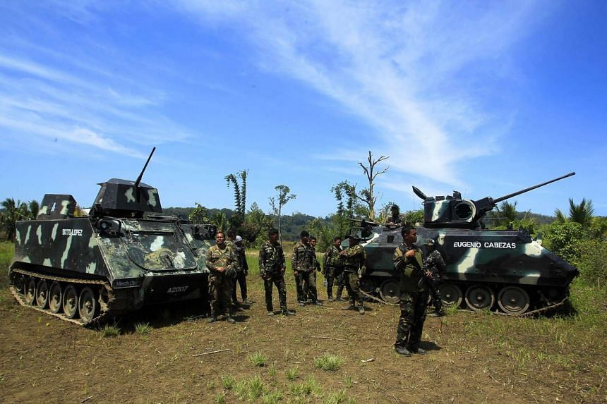 Philippine soldiers standing guard next to tanks in Butig town, Lanao del Sur on March 1, 2016, where gunmen waving ISIS flags attacked a military outpost.