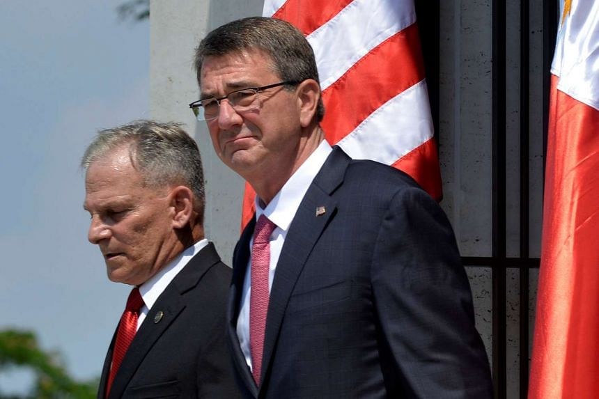 US Defence Secretary Ash Carter (right) walking with Manila American Cemetery deputy superintendent Hubert Caloud after a wreath laying ceremony in Taguig, Metro Manila, on April 14, 2016.