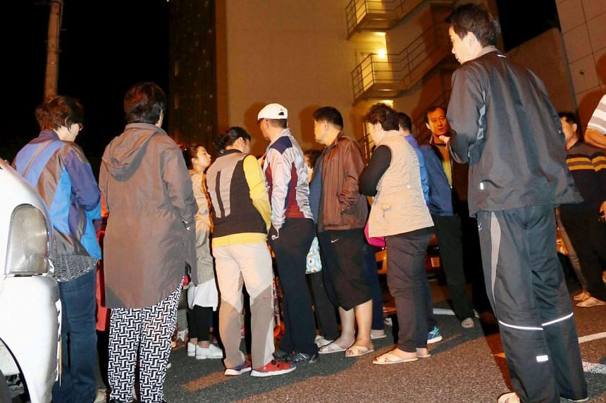 People standing outside a hotel in Kumamoto city after being evacuated following an earthquake, on April 14, 2016.