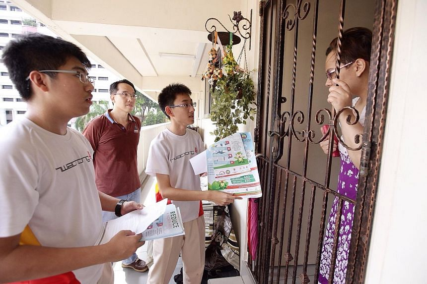 Ryan Kang (left), 15, and Thio Leng Kiat, 16 (third from left), are two of the participants in North West CDC's Reduce@North West scheme, where students go door to door to share energy-saving tips.