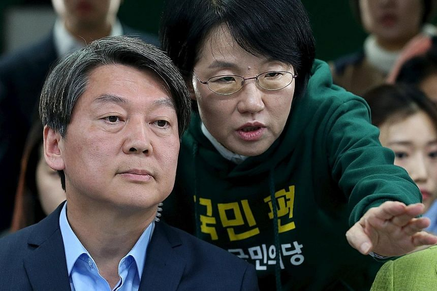 Voters receiving their ballot papers at a polling station in Seoul. Yesterday's voter turnout was about 58 per cent of the more 42.1 million eligible voters. Some analysts say a coalition government may emerge with the People's Party, led by Mr Ahn C