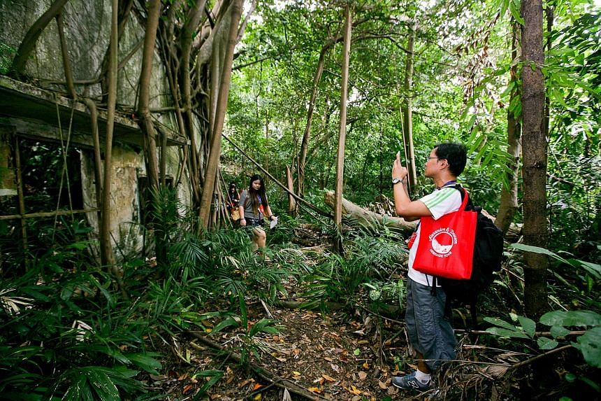 A participant of the Dawson and Alexandra tour taking photographs of an abandoned bunker in Kay Siang Road. Participants listening to long-time Queensway resident Paul Fernandez, 74, sharing his memories of the estate during a Dawson and Alexandra he