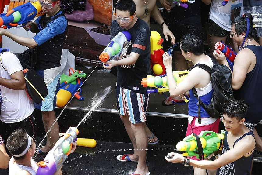 Tourists with water guns joining in the annual Songkran celebrations for the Buddhist new year in Bangkok yesterday.