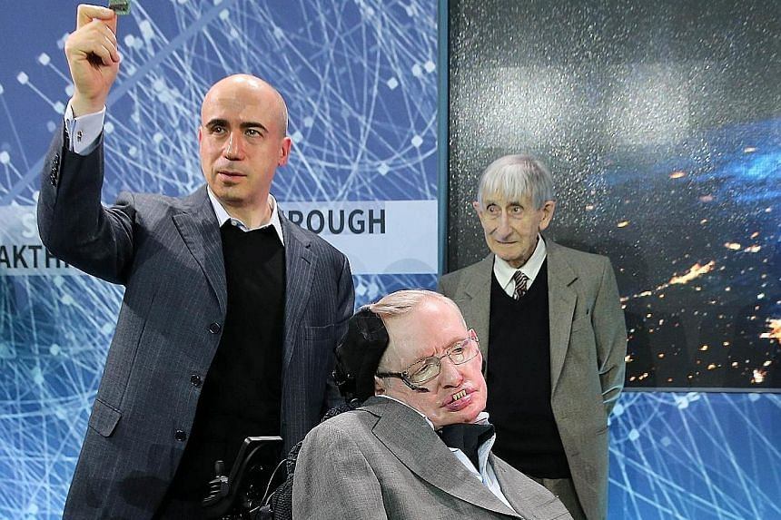 """Mr Milner holding up a prototype of the """"Star Chip"""", a small robotic spacecraft, at the announcement of the """"Breakthrough Starshot"""" initiative at One World Observatory in New York City on Tuesday. With him are Prof Hawking (seated) and English-born A"""