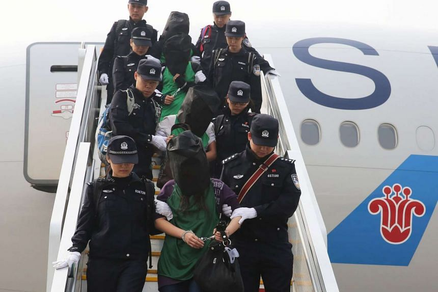 Police escort a group of people wanted for suspected fraud in China, after they were deported from Kenya, as they get off a plane after arriving at Beijing Capital International Airport on April 13