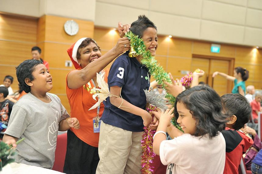 Mrs Angela Perumal-Schooling, volunteer and Singapore Press Holdings' pre-press foreman, playing with some of the young beneficiaries from charity organisations on Dec 17, 2013.
