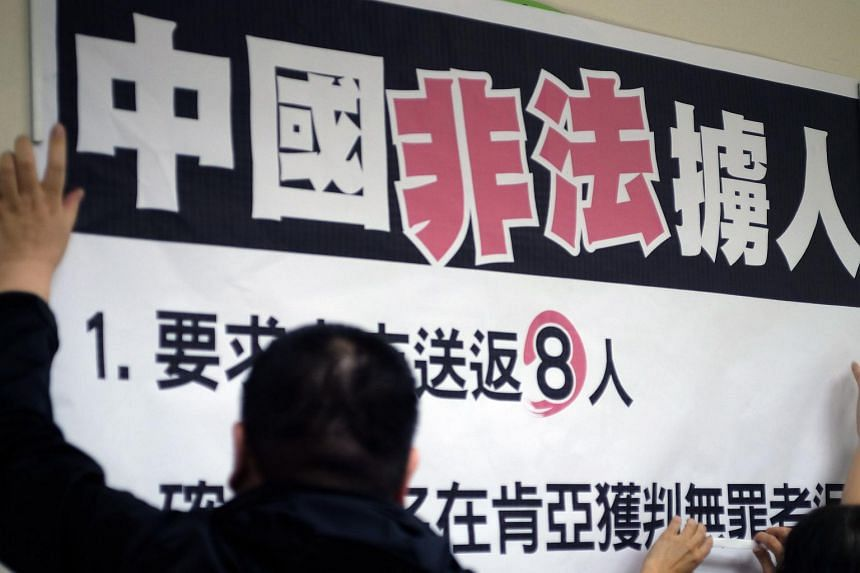 """Workers paste a sign reading """"China illegally abducts Taiwanese people"""" at a press conference organised by lawmakers from the Democratic Progressive Party (DPP) in Taipei, on April 12, 2016."""