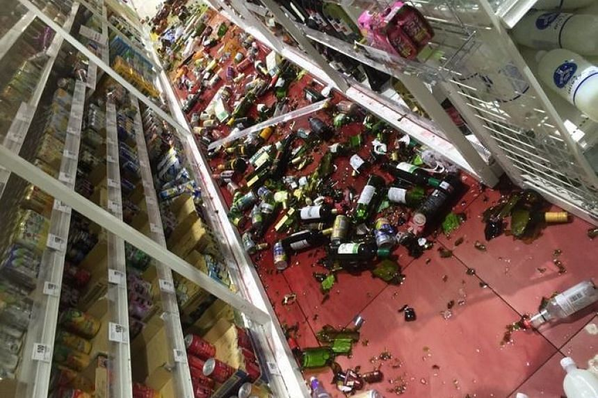 Wine and broken glass bottles are seen on the floor of a convenience store in Kumamoto prefecture.