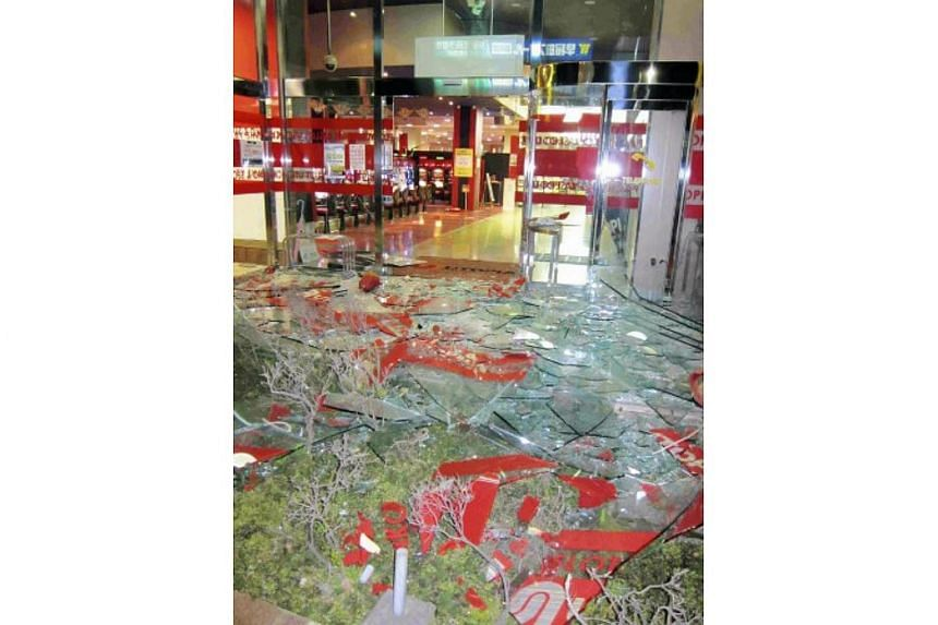 Shattered glass lies on the ground outside a pachinko parlour in Kumamoto city after a 6.4-magnitude quake struck on April 14, 2016.