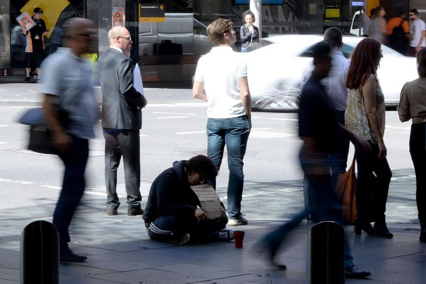 A homeless man waits for charity in the central business district of Sydney.