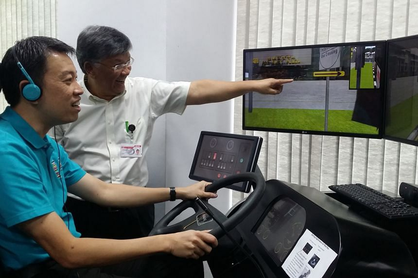 MP Melvin Yong tries his hand at manoeuvring a bus on a simulator at the SMRT Training School.