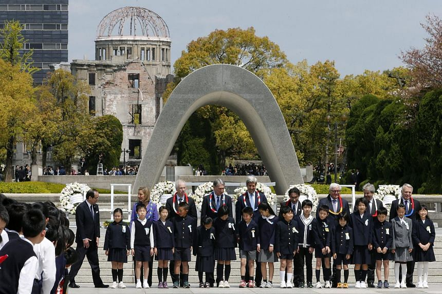 The Group of Seven countries' foreign ministers pose for a group photo with children at Hiroshima Peace Memorial Park, on April 11, 2016.