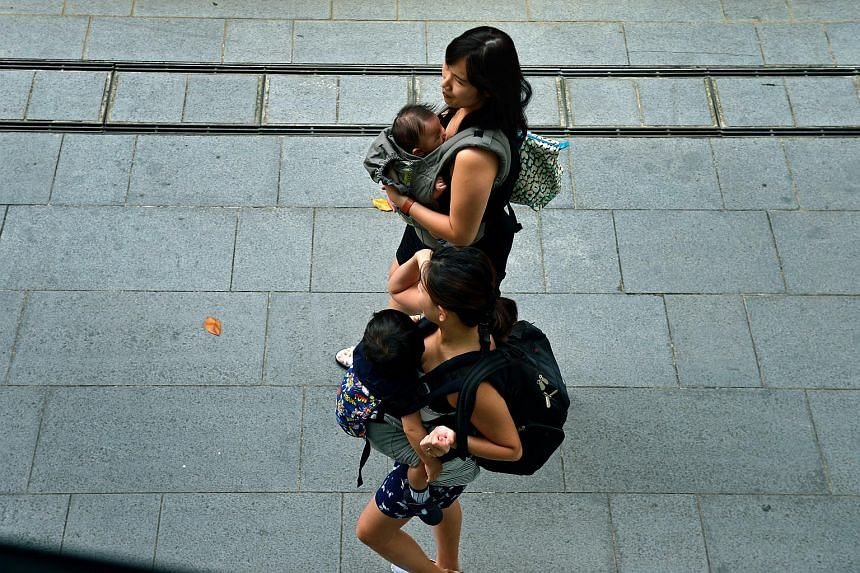 Mothers with babies slung in front of them as they walk along Orchard Road.