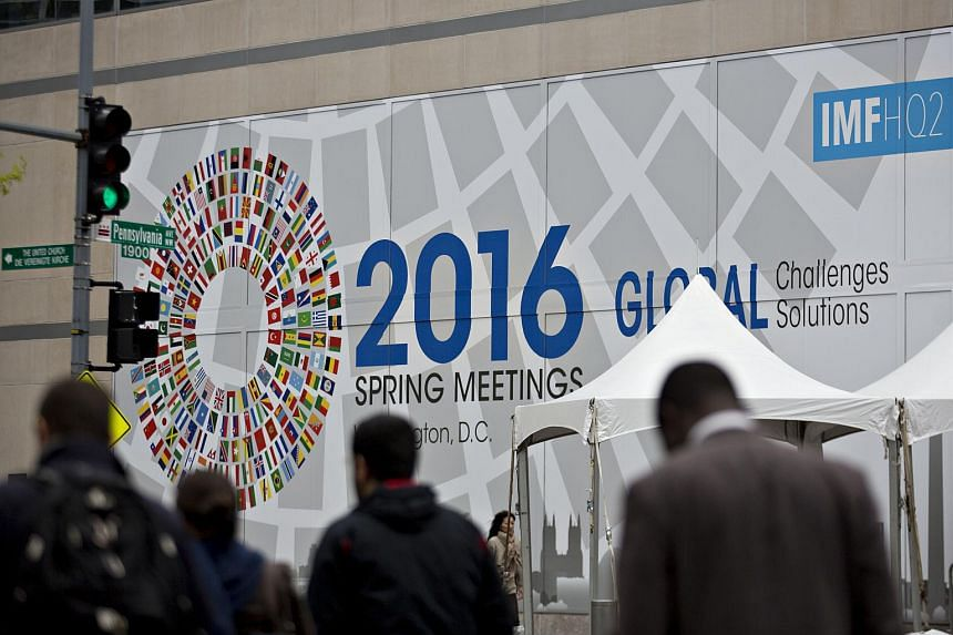 Pedestrians walk near a sign for the spring meetings of the International Monetary Fund and World Bank in Washington, on April 12, 2016.