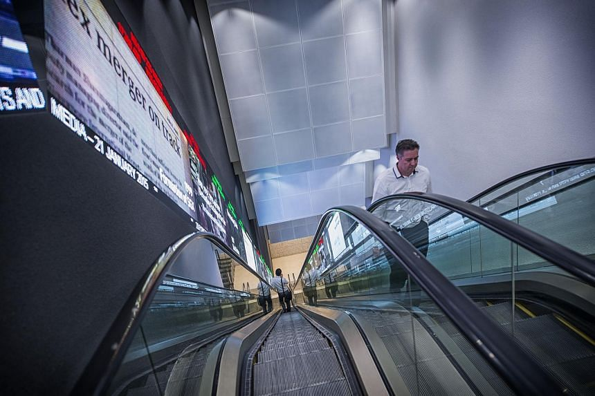 Pedestrians ride an escalator past an electronic screen and ticker board that indicates stock figures at the Singapore Exchange Ltd. (SGX) headquarters in Singapore.