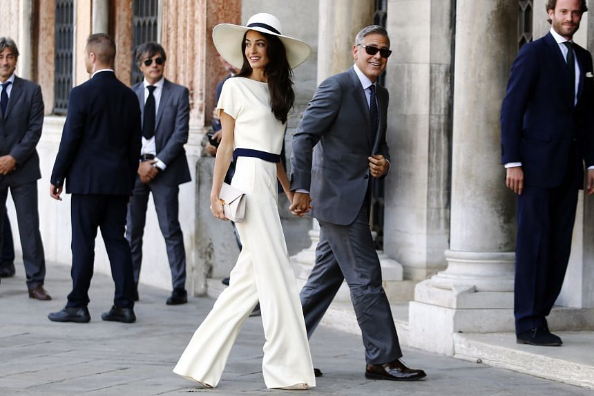 Amal Clooney wore a Stella McCartney white two-piece custom suit for her legal civil ceremony to George Clooney (both centre) in Venice in 2014.