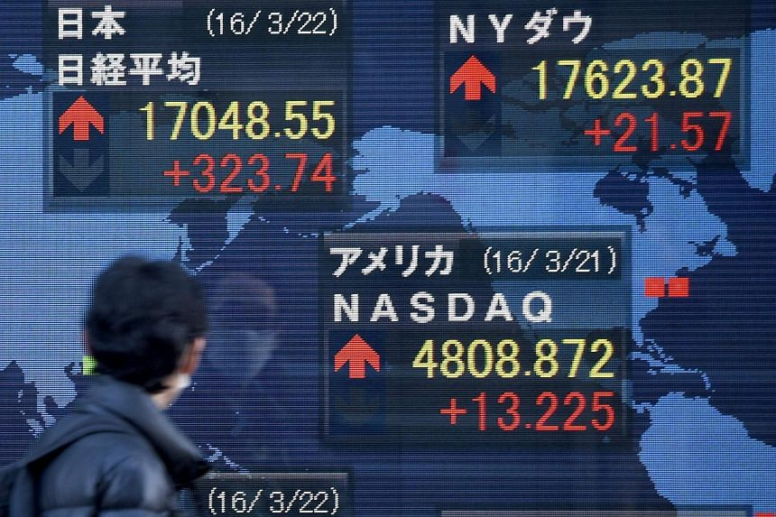 A man looks at a quotation board flashing key indexes of Tokyo and New York stock markets in front of a securities company in Tokyo.