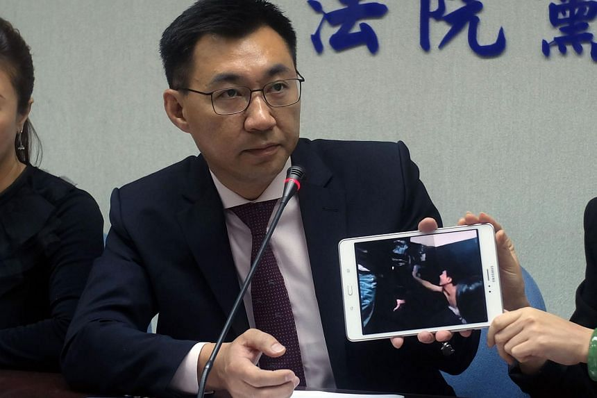 Johnny Chiang, a legislator from the Kuomintang (KMT) party, displays a video clip showing Taiwanese detented at a police station in Kenya.