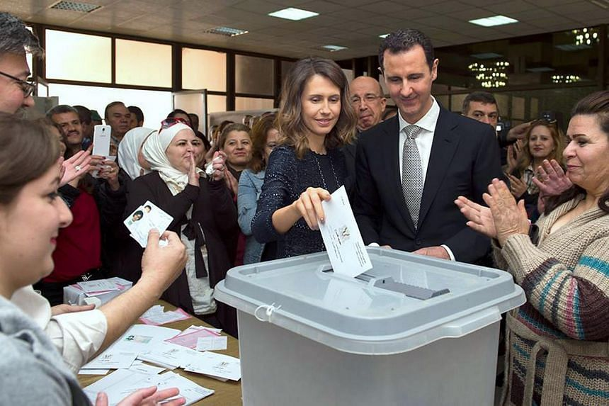 Syrian President Bashar al-Assad (right) and his wife Asma voting at a polling station in Damascus during the parliamentary elections, on April 13, 2016.