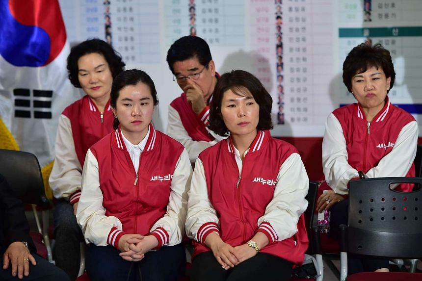 Members of the ruling Saenuri Party react as they watch a live TV broadcast reporting the results of parliamentary elections in Seoul, on April 13, 2016.