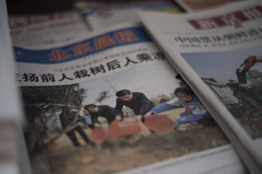 A newspaper shows a front page photo of Chinese leaders including President Xi Jinping (centre) attending a tree planting ceremony, at a news stand in Beijing on April 6, 2016.