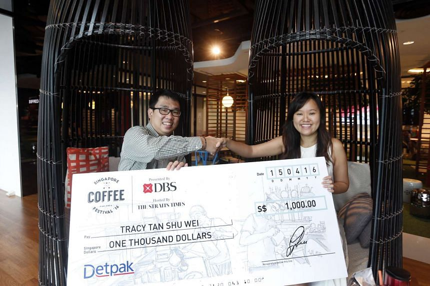 Detpak sales manager Aaron Yeo (left) presenting a $1,000 cheque to Ms Tracy Tan, winner of the Singapore Coffee Festival's Design-The-Cup competition.