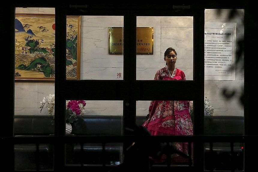 A woman in traditional costume waiting for customers at a North Korean restaurant in Beijing. There are about 130 such restaurants overseas, staffed by workers from the North, most of whom remit revenue to Pyongyang.