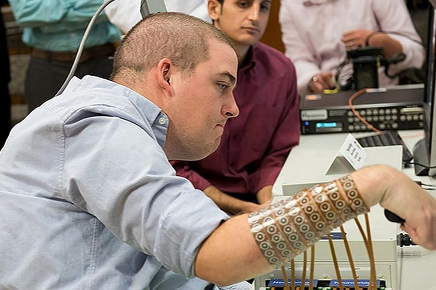Quadriplegic Ian Burkhart (left), 24, using neural bypass technology to control his arm in this picture released by the Ohio State University Wexner Medical Centre in Columbus, Ohio. The American was left paralysed from the chest down after a diving