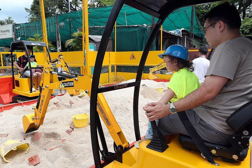 Mr Victor Khoo (right), 37, operating an excavator at Diggersite with his daughter Sophie, two. The owner, Mr Lim, hopes that his enterprise will improve perceptions of blue-collar jobs.