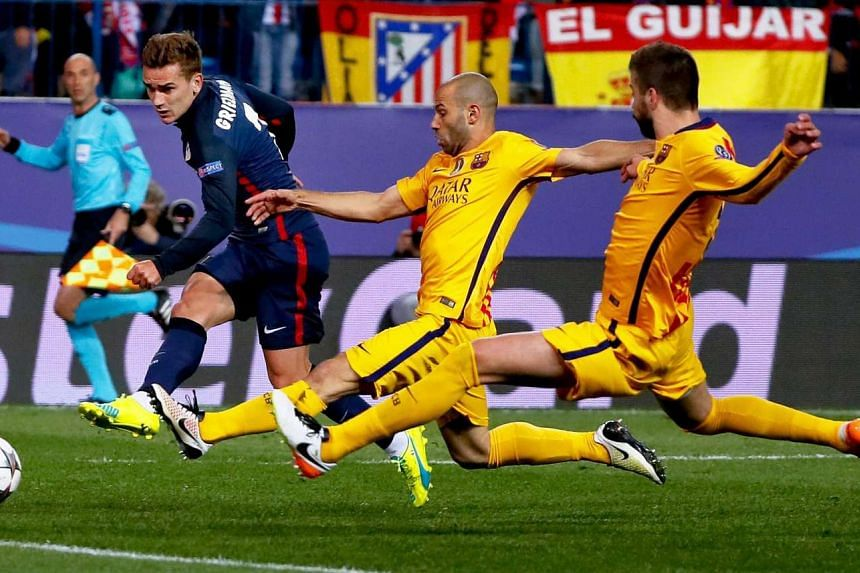 Atletico Madrid's forward Antoine Griezmann (left) in action against FC Barcelona's defenders Gerard Pique (right) and Javier Mascherano.