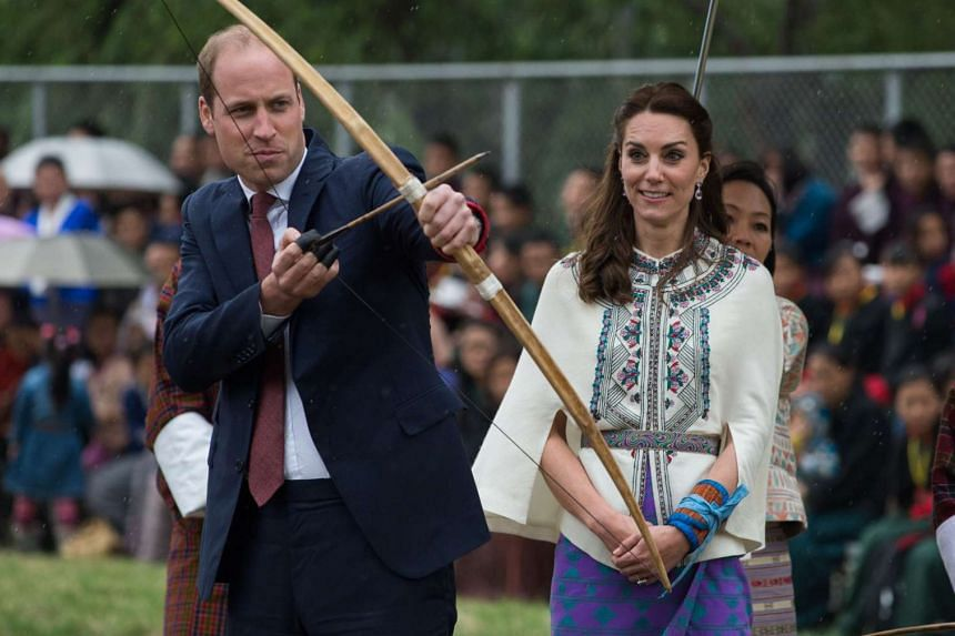 Britain's Duchess of Cambridge Catherine (right) looks on as Duke of Cambridge Prince William fires an arrow at the Changlingmethang National Archery ground in Thimphu, on April 14, 2016.