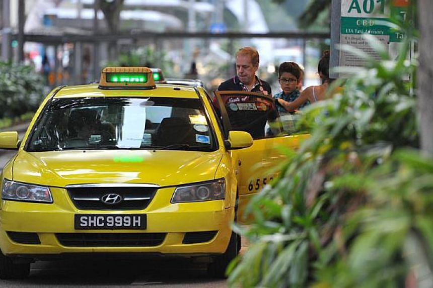 Passengers boarding a ComfortDelgro taxi at the Lucky Plaza taxi stand.