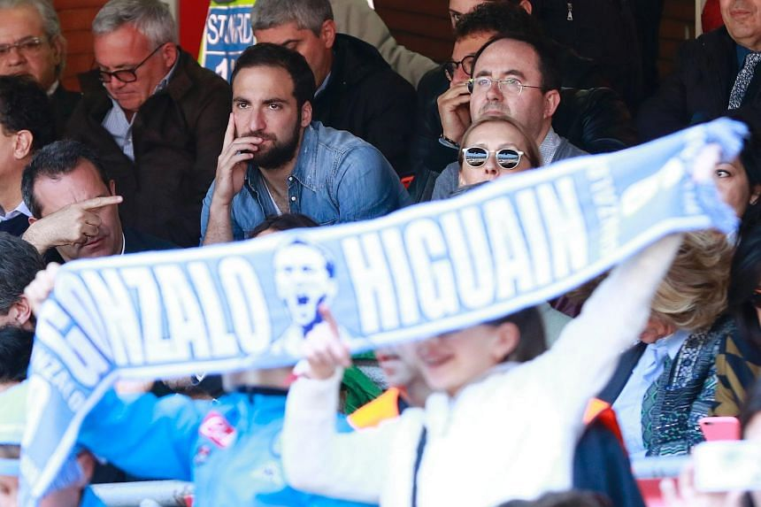 Napoli's Argentinian-French forward Gonzalo Higuain sitting in the stands after being suspended for 4 matches, prior to the start of the Italian Serie A football match SSC Napoli vs Hellas Verona FC on April 10, 2016.