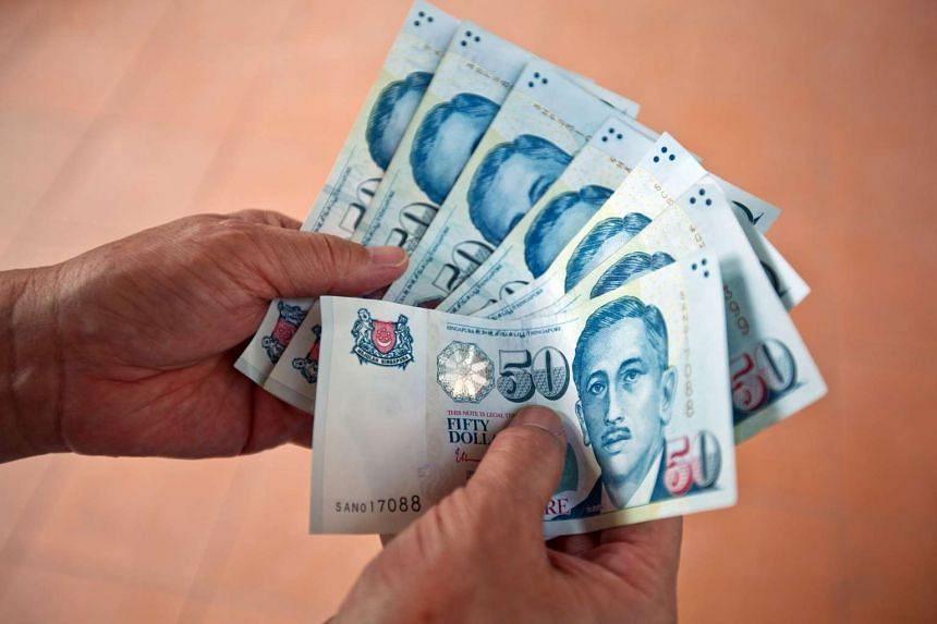 Singapore dollar banknotes are arranged for a photograph in Singapore, on April 9, 2016.
