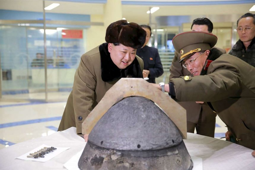 North Korean leader Kim Jong Un looking at a rocket warhead tip after a simulated test of atmospheric re-entry of a ballistic missile, at an unidentified location in this undated file photo released by North Korea's Korean Central News Agency (KCNA)