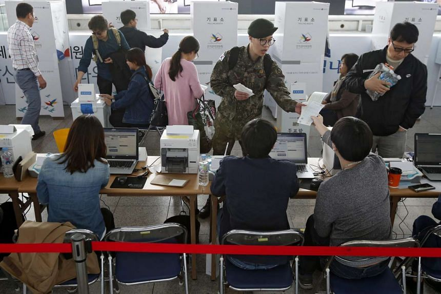 South Korean people receive their ballot to cast at polling station in Seoul, South Korea, on April 8, 2016.