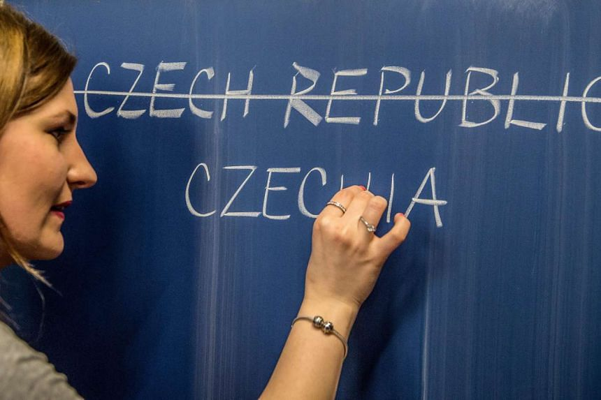 A school teacher writes the possible new English name Czechia for the Czech Republic on a blackboard in Prague on Thursday.