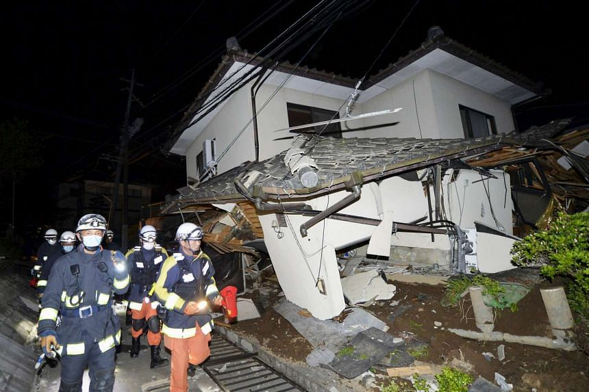 Firefighters check a collapsed house after an earthquake in Mashiki town early Friday morning (April 15).